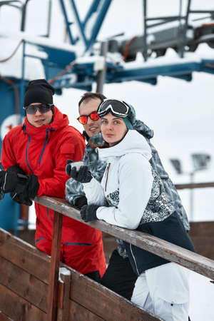 group of skiers friends on the mountain are resting and drinking coffee from a thermos on the background of the ski lift Reklamní fotografie