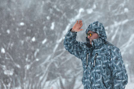 Portrait of serious man in sunglasses and warm clothes walking in snowy forest