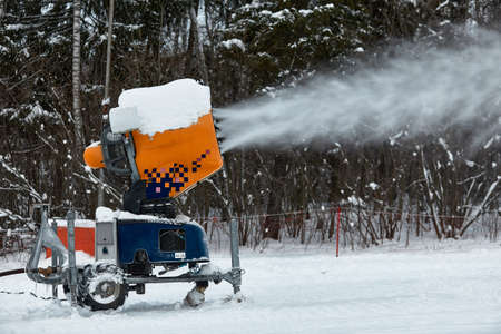 Snow cannon spraying out a fresh dusting of snow on the ski slopes. Reklamní fotografie