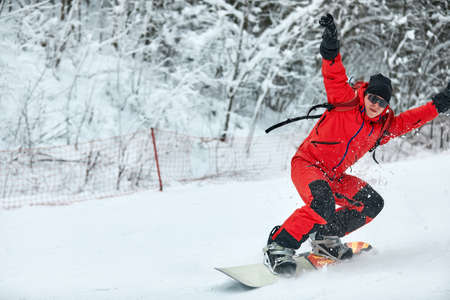 Male snowboarder in a red suit rides on the snowy hill with snowboard, Skiing and snowboarding concept Reklamní fotografie