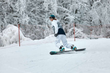 cheerful woman riding on snowboard in the mountains in winter. woman in white ski suit