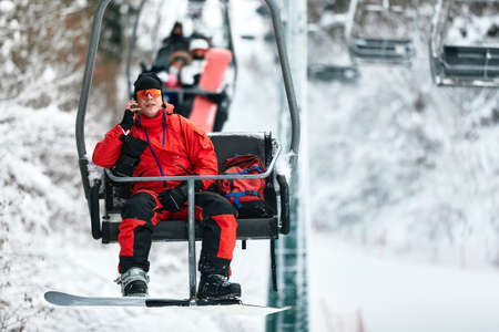 Skier sitting at ski lift talking on the phone in high mountains during sunny day. Winter sport and recreation, leisure outdoor activities.