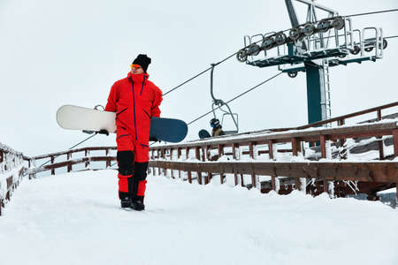 Male snowboarder in a red suit walking on the snowy hill with snowboard, Skiing and snowboarding concept Reklamní fotografie