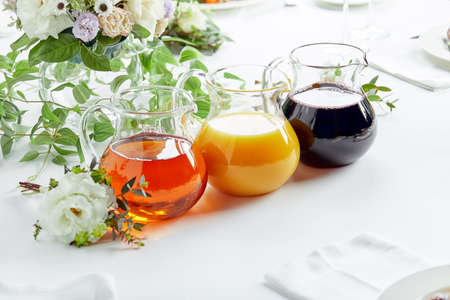 Jugs with different juices on event catering. Apple, orange, cherry and tomato juices Reklamní fotografie