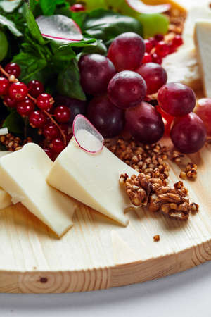 Different varieties of cheese with walnuts and grapes. Reklamní fotografie