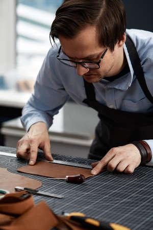 leather craftsmen working making measupenets in patterns at table in workshop studio Reklamní fotografie