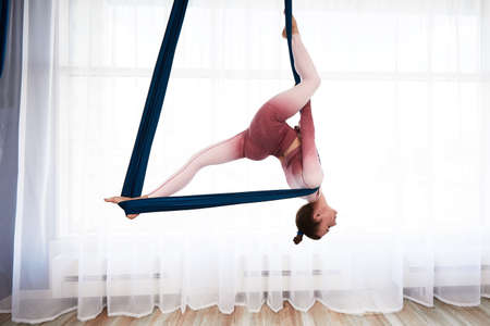 Cheerful sporty woman wearing top and leggings performing anti-gravity yoga exercise at spacious health club with panoramic windows