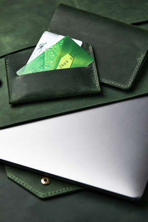Group of green leather goods handmade on a wooden table. Top view, close-up. Reklamní fotografie