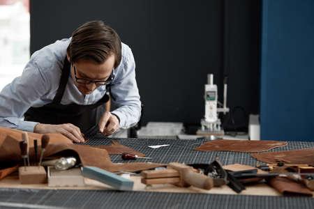 Skilled leather manufacture worker cutting some samples Reklamní fotografie