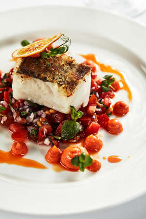 Black cod with vegetables, an appetizing piece of grilled black cod garnished with stewed vegetables on a white plate Imagens