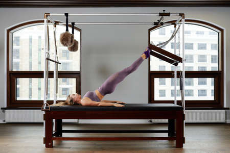 Modern equipment Cadilac reformer for Pilates in the gym, Concept of health and rehabilitation, instructor performs exercises on the reformer to correct the musculoskeletal system. Imagens