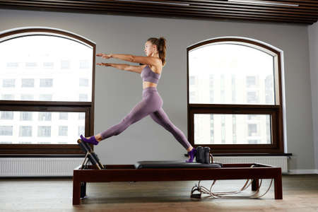 Modern equipment studio reformer for Pilates in the gym, Concept of recovery and rehabilitation, the instructor performs exercises on the studio reformer to correct the musculoskeletal system.
