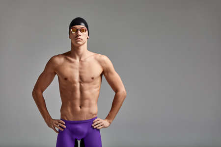 Young male swimmer preparing for the start, half-length portrait of a swimmer in a mask and a hat, gray background, copy space, swimming concept.