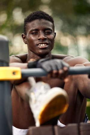 A smiling African American athlete performs abdominal exercises, an athlete in excellent physical shape does abdominal exercises on the street in the sports field.