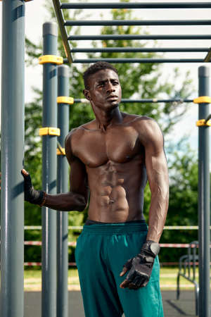 Athlete resting between outdoor exercises, outdoor exercise, African American exercising on the sports ground.
