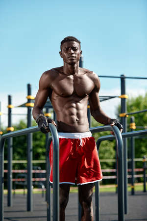 Young athlete afroamericatsen, exercising on the uneven bars, an athlete in excellent physical shape doing exercises on the street on the playground