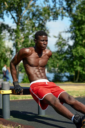 Athlete doing push-ups on the sports ground, African American athlete doing push-ups on outdoor gym equipment, sports lifestyle, striving for success