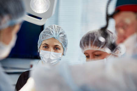 Concentrated Surgical team operating a patient in an operation theater. Well-trained anesthesiologist with years of training with complex machines follows the patient throughout the surgery. Imagens