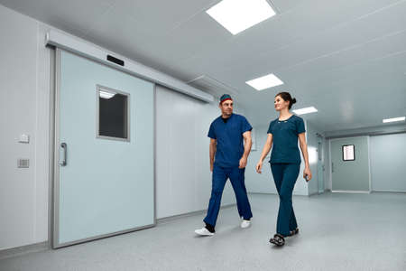 Doctors surgeons walk along the corridor of the clinic in suspense, preparing for a complex operation.