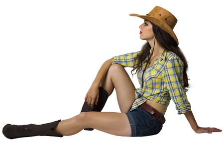 Cowgirl sitting.Attractive young woman in cowboy clothes isolated on white photo