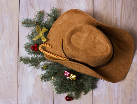 American western cowboy hat with Christmas decoration on wood background