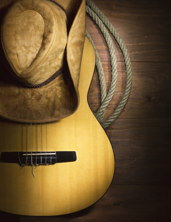 American Country music with guitar and cowboy hat on wood background photo