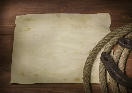 Old paper background with cowboy lasso and horseshoe on wood texture