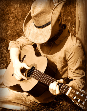 west: Cowboy  plays guitar on ranch .Country music