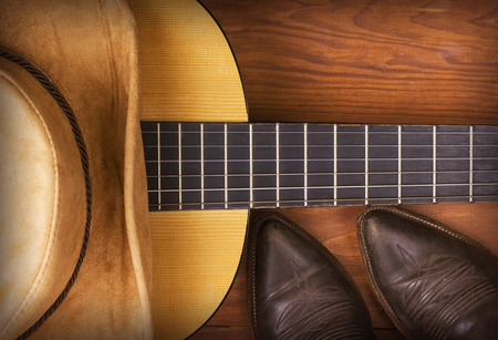 botas vaqueras: La m�sica country americana con guitarra y de vaquero zapatos en el fondo de madera