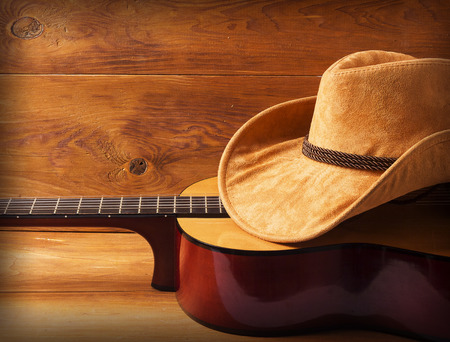 Guitar and cowboy hat on wood background for text or design