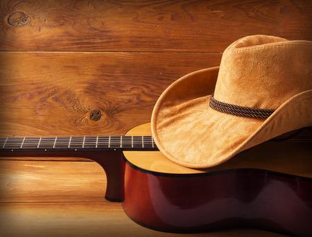 vaquero: Guitarra y sombrero de vaquero en el fondo de madera para el texto o el diseño