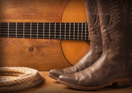 Country music with guitar and cowboy shoes on wood texture background Stockfoto
