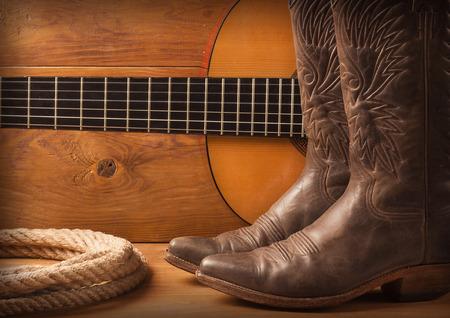 botas vaqueras: La música country con la guitarra y de vaquero zapatos en el fondo de textura de madera