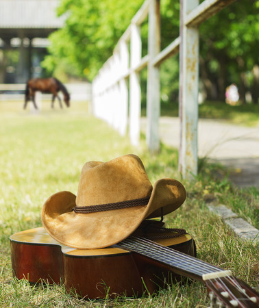 cowboy hat: cowboy hat and guitar on American ranch landscape.Country music