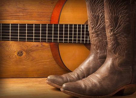 botas vaqueras: La m�sica country americana con guitarra y de vaquero zapatos en la madera Foto de archivo