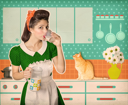 vintage kitchen: Attractive retro woman drinking glass of fresh milk in her kitchen room.Vintage old poster Stock Photo