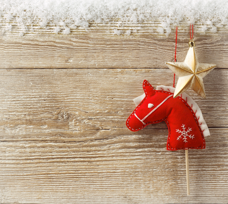Christmas cowboy background with toy horse and star on wood texture for text