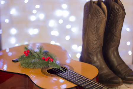 Country music christmas with acoustic guitar and cowboy shoes on wood