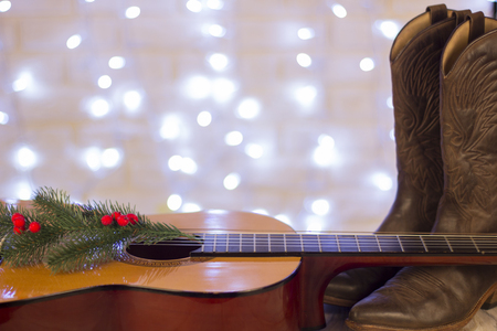 Country music christmas background with acoustic guitar and cowboy shoes
