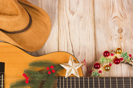 Cowvoy christmas wood background with guitar and cowboy western hat