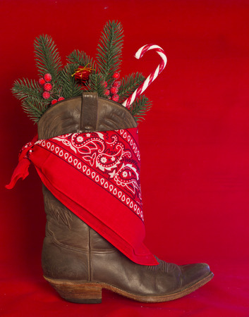 American West traditional cowboy boot and red bandanna on christmas red background for text
