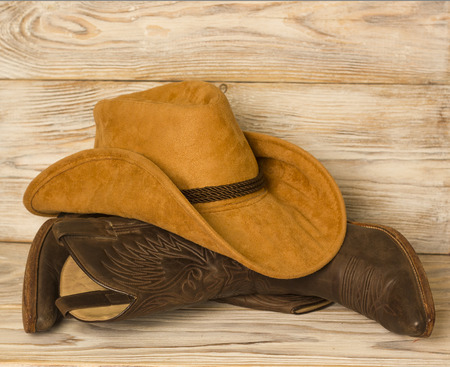 American West cowboy shoes and hat on wood texture background for text