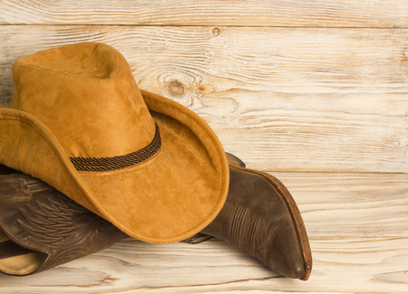 American West cowboy boots and hat on wood texture background for text Reklamní fotografie