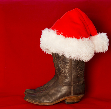 Cowboy Christmas background with traditional American cowboy boots and red Santa hat