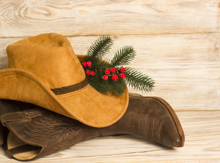 Cowboy Christmas.American West traditional boots and hat on wood background texture