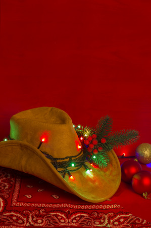 Cowboy Christmas.American West hat and bandanna on christmas red background for text