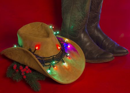 Cowboy Christmas.American West traditional boots on christmas red background for text