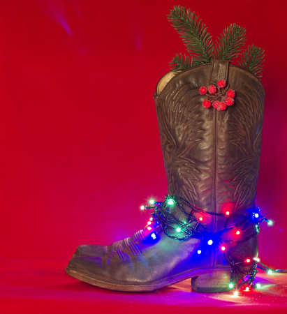 American West traditional boots on christmas red background for text Stock Photo