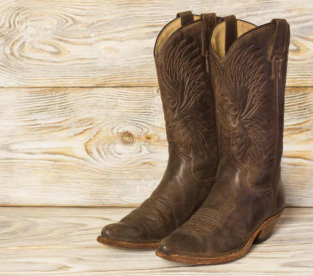 Leather West American cowboy boots on wood background