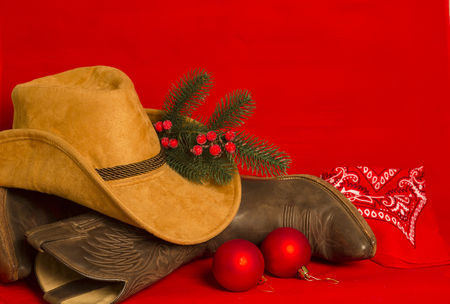 Cowboy Christmas card.American West traditional boots and hat on christmas red background for text